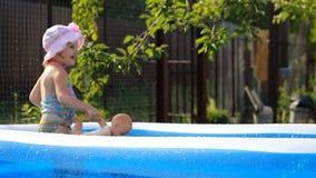 hildflickan badar i en pöl under sprejen av vatten lager videofilmer