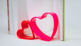 hilding一本开放日志书的页的红色和淡紫色心脏 免版税库存照片
