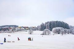 Hildren滑冰在雪的冬天跑的雪橇 免版税库存图片