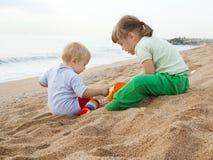 Hildren che gioca con la sabbia in mare Fotografie Stock Libere da Diritti