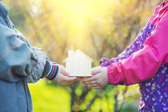 Сhildren hold little toy house in hands. Royalty Free Stock Photo