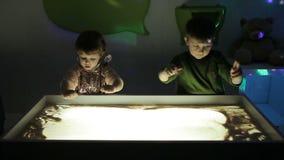 Hildren remis z ich rękami na piasku z iluminacją zbiory