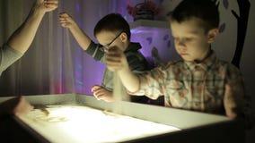 Hildren remis z ich rękami na piasku z iluminacją zdjęcie wideo