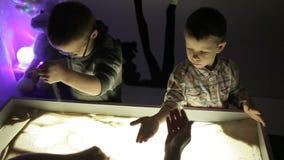 Hildren remis z ich rękami na piasku z iluminacją zbiory wideo