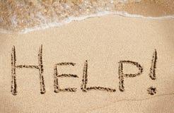 Hilfe handgeschrieben auf Sand des Strandes Lizenzfreie Stockfotos
