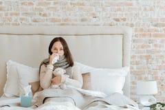 Hilflose Frau, die unter Kälte im Schlafzimmer leidet Lizenzfreies Stockbild