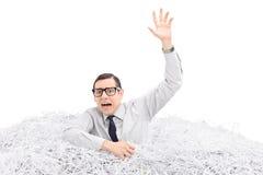Hilfloser Mann, der in einem Stapel des zerrissenen Papiers ertrinkt Lizenzfreie Stockbilder