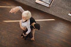 Hilfreiche Tanzcouch, die alte Dame am Ballsaal anweist Stockfotografie