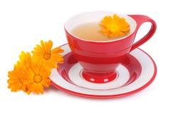Hilfreicher Tee mit den Ringelblumenblumen lokalisiert stockbild