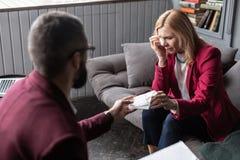 Hilfreicher Therapeut, der Kunden sich fühlen emotional und dem Schreien Serviette gibt stockfotografie