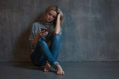 Hilfslinie, psychologische Unterstützung Leidende junge Frau, die in einer Ecke mit einem Telefon in ihrer Hand sitzt lizenzfreie stockfotografie
