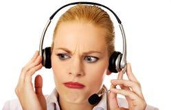 Hilfslinienbetreiber der jungen Frau versucht, etwas durch Kopfhörer zu hören Lizenzfreies Stockfoto
