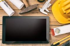 Hilfsmittel und Tablettecomputer Tablet mit schwarzem leerem Bildschirm, Projektbauplänen und Technikwerkzeugen auf hölzernem Sch stockfotos