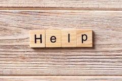 Hilfswort geschrieben auf hölzernen Block Hilfetext auf Tabelle, Konzept Stockbilder