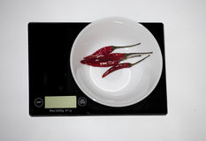 Сhili peppers on a digital white kitchen scale. (weighing produ Stock Photo