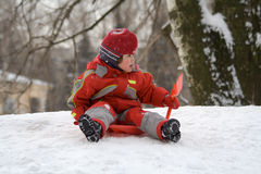 On a hill. The little girl sits on an ice slope Royalty Free Stock Image