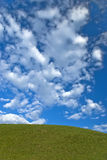 Hill. Green hill under the cloudy blue sky Stock Photos