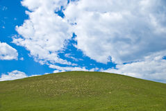 Hill. Green hill under the cloudy blue sky Royalty Free Stock Image