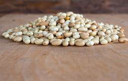 Hill of beans on the wooden table. Hill of beans on a wooden table with wood background Stock Photography