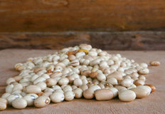 Hill of beans on the wooden table. Hill of beans on a wooden table with wood background Stock Photos