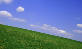 Hill and blue sky. Clouds in the sky above a green hill Royalty Free Stock Image