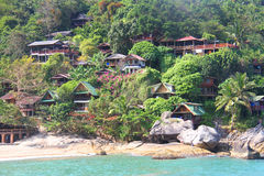 Hill with bungalows on tropical beach Royalty Free Stock Image