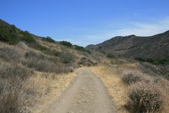 Hill Canyon. Trail through a field beneath blue sky, California Royalty Free Stock Photos