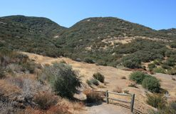 Hill Canyon. Trail through a field beneath blue sky, California Stock Photos