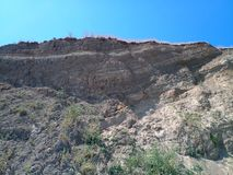 Hill with cliff, layers of clay and soil. Hill with a cliff, layers of clay and soil royalty free stock images