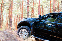 Hill in coniferous forest with a big black car Royalty Free Stock Image