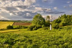 On the hill. Cross in a spring landscape under cloudy sky Stock Photo