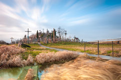 Hill of crosses near Siauliai, Lithuania, Europe. Famous hill of crosses near Siauliai, Lithuania, Europe. Yellow grass in foreground and blue cloudy sky in Royalty Free Stock Photos