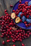 Hill dogwood berries and plums on  plate Stock Photos
