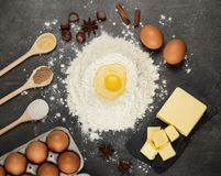 Hill of flour, broken egg on top, butter and spices in spoons on work surface Royalty Free Stock Images