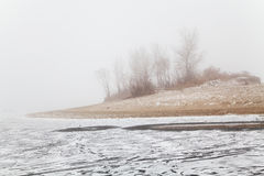 Hill in the fog on a winter frozen river beach Royalty Free Stock Images