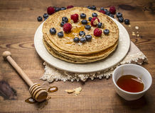 Hill fresh pancakes on a white plate with napkin  with honey and honey spoon, different berries and a cup of tea on rustic wooden Stock Photo