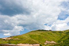 Hill in the grassland. Under blue sky white cloud Stock Images