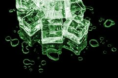 Hill of green ice cubes on a black glass with water drops around. stock image