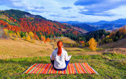 On a hill among high mountains a girl rests in a lotus position. Stock Photo