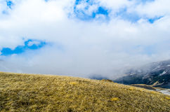 A hill inside the cloud. A meadow in mountains of Caucasus with clouds high in the sky Stock Photos