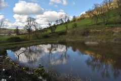 Hill and lake or reservoir, reflection of cloudy sky in the water, welsh flora, pure nature in spring, Shropshire Hills, Wales UK Stock Image