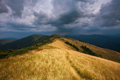 Hill in mountains on background of dramatic sky storm clouds Stock Photos