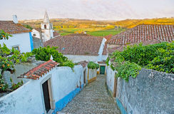On hill in Obidos. The descent along the medieval street with a view on historic housing, belfry of St Mary Church and the juicy green fields and meadows on Stock Images