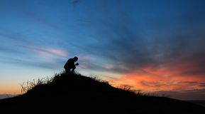 Hill of Prayers. Man kneeling on top of a hill after sunset stock photo