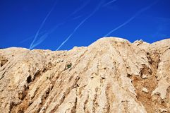 Hill in quarry with airplane lines on the sky Stock Image