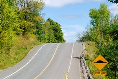 Hill on road with speed bump sign. Hill on country road with yellow speed bump warning sign royalty free stock images