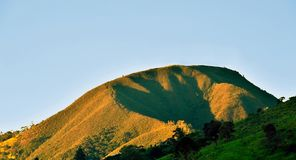 A hill`s peak hit by the sunlight over a clear blue sky background Royalty Free Stock Photo