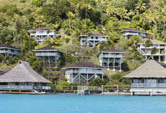 Hill slope by the sea and lodges on  slope. Polynesia. Royalty Free Stock Photo