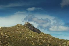 Hill with tin peaks. Hill with twin peaks with  surrounding hillsides covered in scrub and rocks, low clouds and blue sky Royalty Free Stock Photos