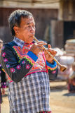 Hill tribe senior man blowing traditional pipe, music equipment Stock Photos